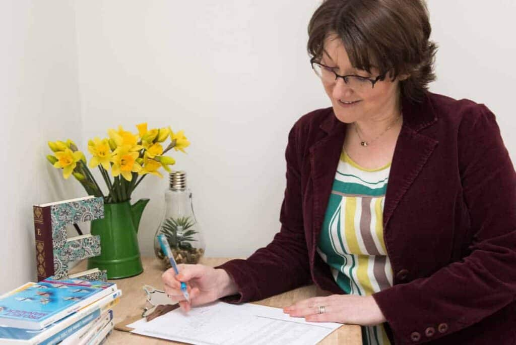 Elizabeth Harrin working at a desk with flowers on